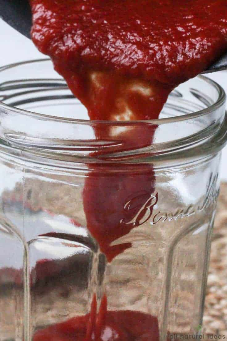 Pouring homemade paleo ketchup into jar