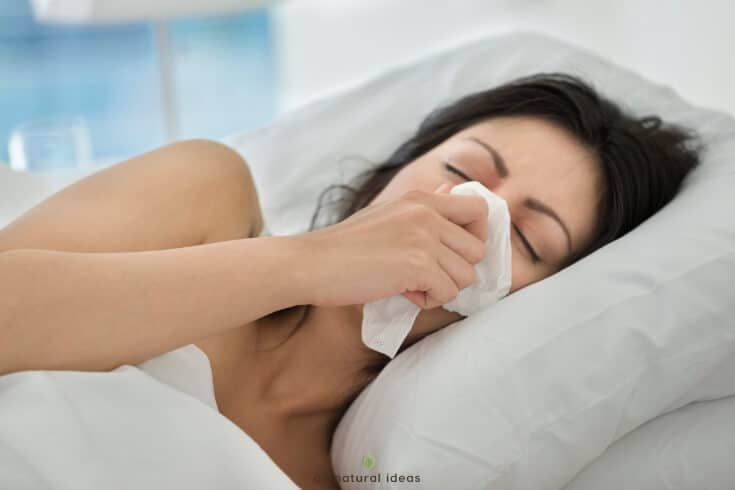 Woman in bed blowing nose. Try essential oils for congestion.